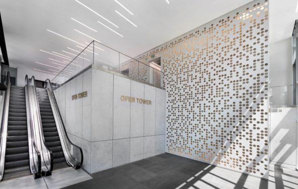 חיפוי קירות לובי בבניין משרדים בפתח תקווה. קוריאן בחיתוך CNC ממוחשב מין משרביה עם שילוב תאורה ברקע