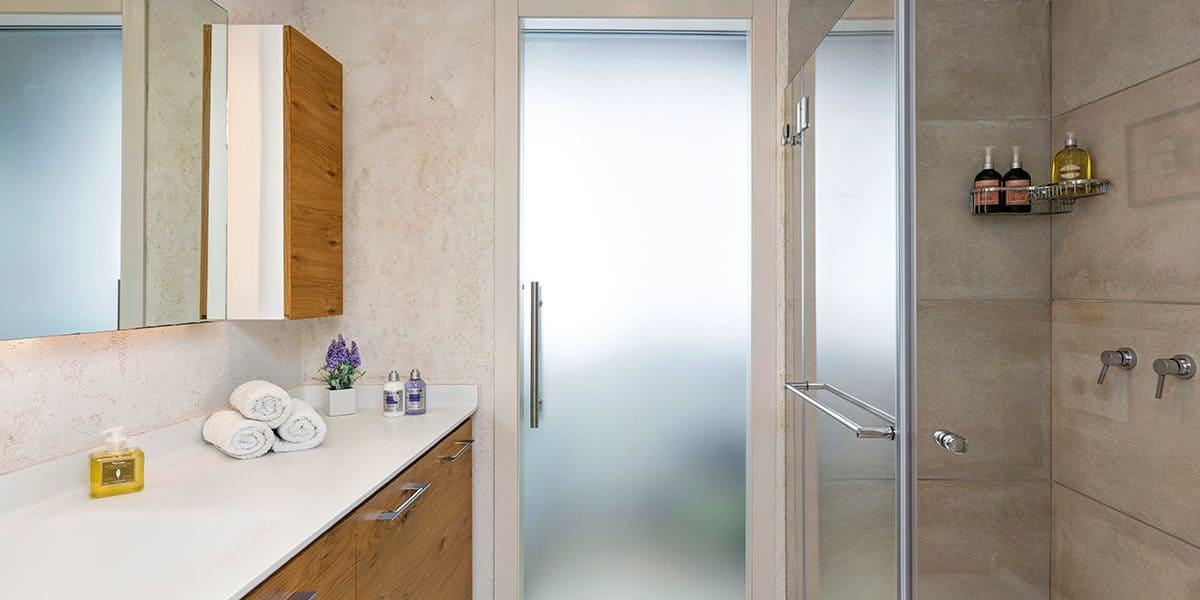 חלל רחצה המשלב אלמנטים כמו קוריאן עם זכוכית ושיש טבעי